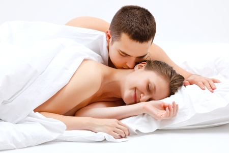 Young couple in bed, man awakening the woman, by kissing her neck photo