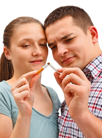 Young couple breaking apart cigarette, meaning stop smoking. Warning: focus on cigarette! Stock Photo - 8922939