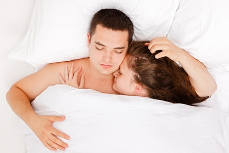 Top view of a young couple sleeping together in bed photo