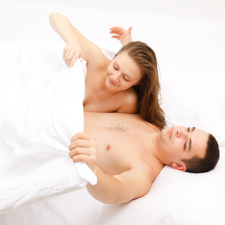 Young couple in bed, woman looking at the mans private part
