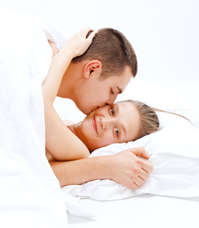 Young couple in bed, man kissing the happy woman photo