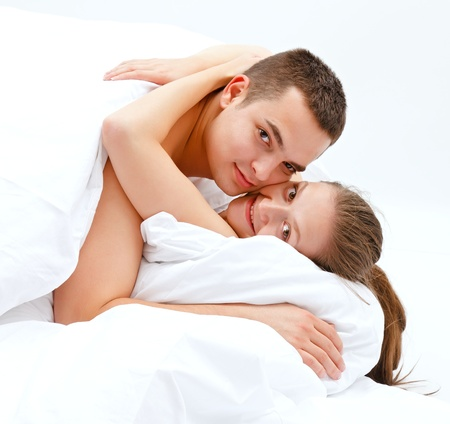 adult sex: Happy young couple hugging in bed, looking to us