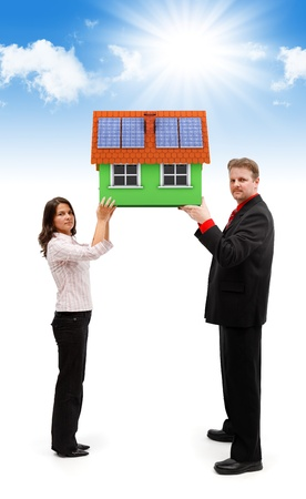 Pareja joven sosteniendo una casa verde con paneles solares