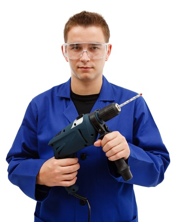 Young worker with goggles holding drilling machine in front of him Stock Photo - 10658870