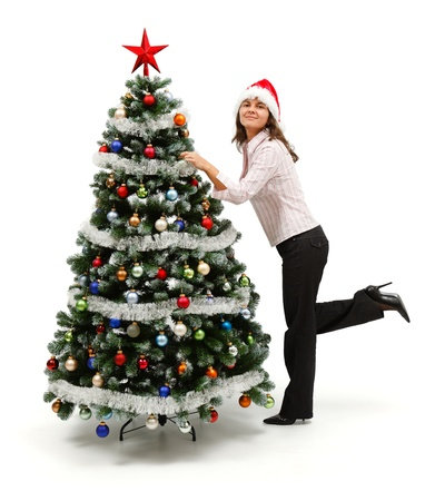 Cute woman standing with one leg raised near decorated Christmas tree Stock Photo - 10658865