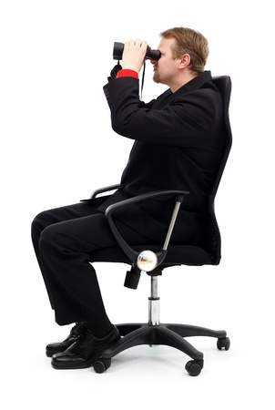 Business man sitting in chair and searching with binoculars photo