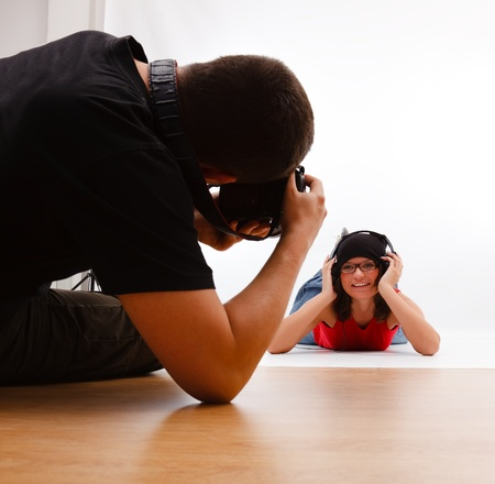 studio photo: Sitting photographer taking photo of smiling woman laying on the floor with headphones and glasses Stock Photo