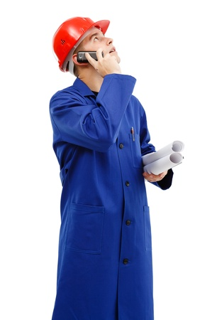 Young engineer looking up while talking on the phone and holding plan rolls in his hand Stock Photo - 10658830