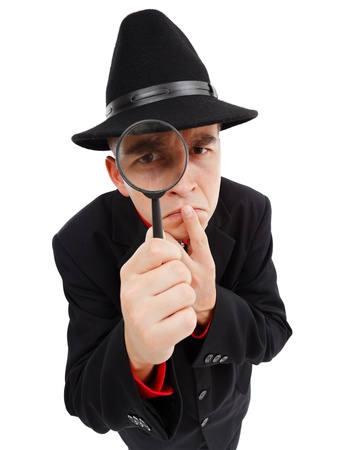 Detective with big hat, thumb on mouth, looking through magnifying glass seriously