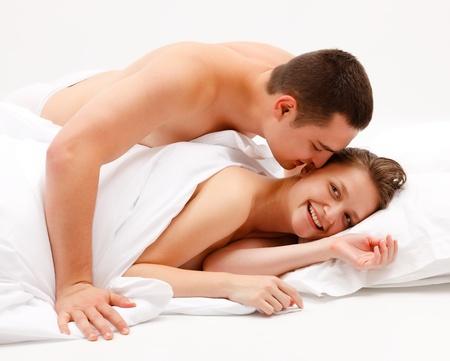 man and woman sex: Молодые голый мужчина склоняется над молодой женщиной веселой лежа в постели Фото со стока