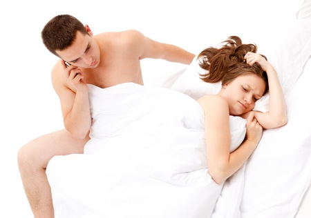 Young couple in bed, man talking on the phone, woman upset photo