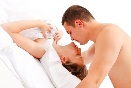 nude in bed: Young naked man leaning over women in bed for a kiss