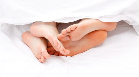 Man and women feet hanging out from under white quilt
