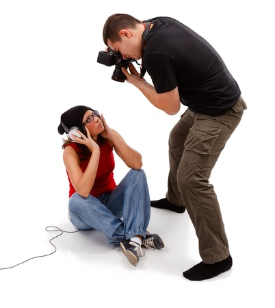 Unshod photographer taking picture from above of sitting female model with headphones and glasses photo