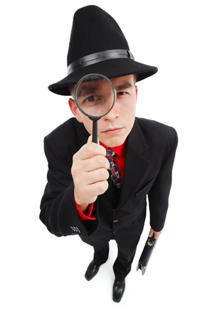 Young detective with briefcase, looking up through magnifying glass photo