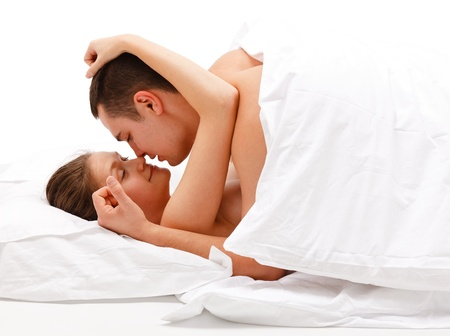 Man on top of woman, caressing each other under the quilt photo