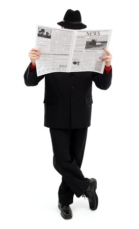 Man in black cloth standing, covering himself and reading news paper Stock Photo - 10826213