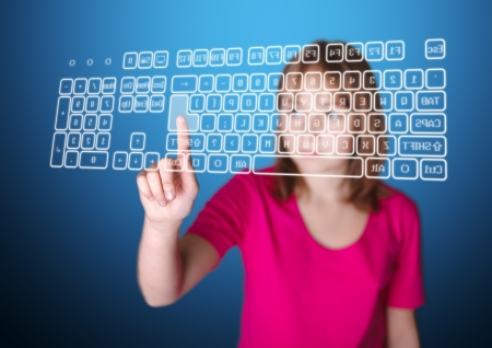 Girl standing in front of virtual screen, pressing enter key on keyboard Stock Photo - 14428327