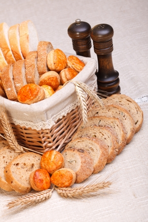 Assorted bakery products sliced, arranged in small basket. Wheat ears in front, salt and pepper behind photo