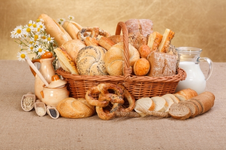bollos: Composici�n de los diversos productos de panader�a en cesta en el fondo r�stico Foto de archivo