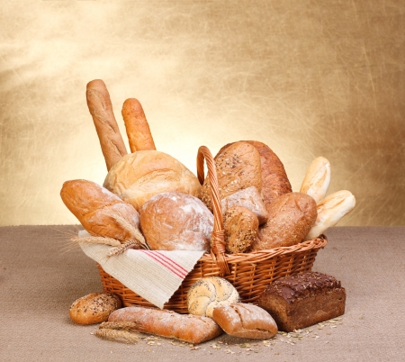 bakery products: Various breads in basket on canvas tablecloth Stock Photo