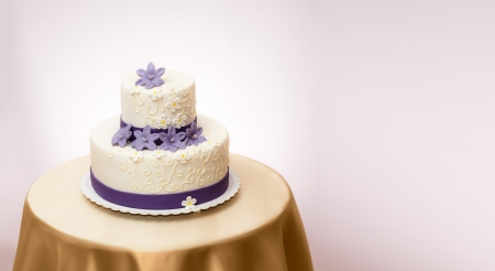 White wedding cake with violet marzipan flower decoration. Copy space on right Stock Photo - 15027958