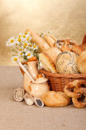 Composition of various baked products in basket on rustic background photo