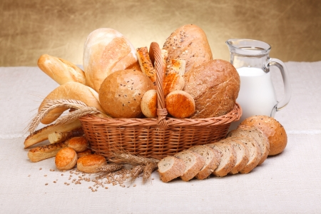 bakery products: Different bread products with milk in jug on canvas