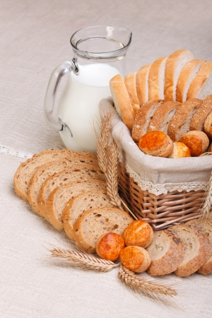 Assorted bakery products sliced, arranged in small basket. Wheat ears in front, milk jug behind Stock Photo - 16059605