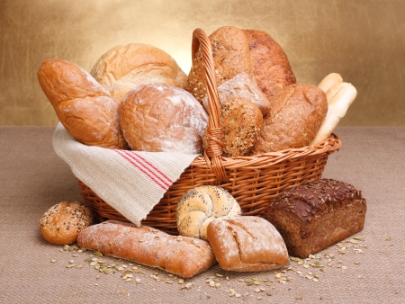 flower baskets: Various breads in basket on canvas tablecloth Stock Photo
