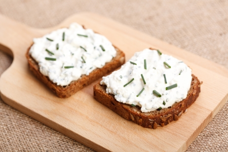 Two slices of spicy buttered bread with green onion on top on wooden board Stock Photo - 16059573