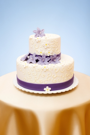 Two-storied white wedding cake with violet marzipan flowers decoration Standard-Bild