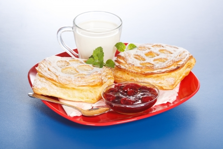 Breakfast: two sour cherry cakes, a cup of milk and jam on red plate Stock Photo - 17688249