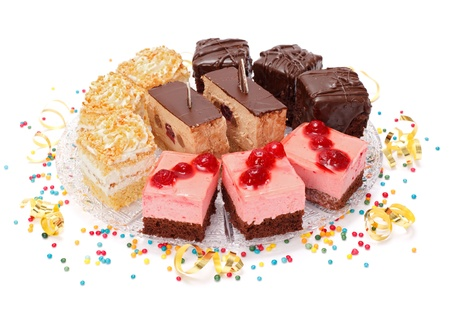 Various sweet creamy cakes on plate with colorful small candies around Stock Photo - 17688148