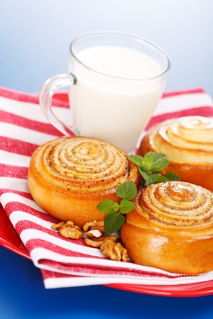 Three cinnamon rolls and jug of milk on red plate, blue background Stock Photo - 17688239