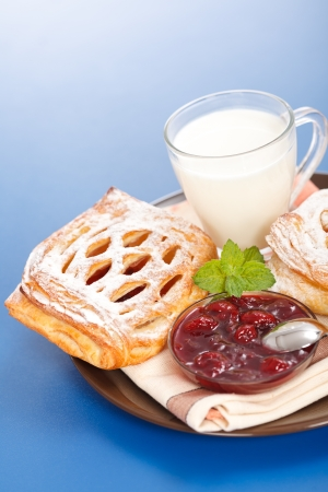 Macro of sour cherry cake, jam and milk on plate, blue background Stock Photo - 17688244