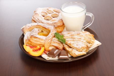 Breakfast  apple, peach, sour cherry cakes and milk on plate, chocolate and peach slices decoration Stock Photo - 17688258