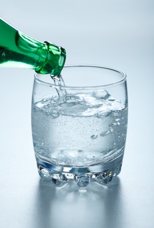 Mineral water being poured into glass from green bottle Stock Photo - 17688234