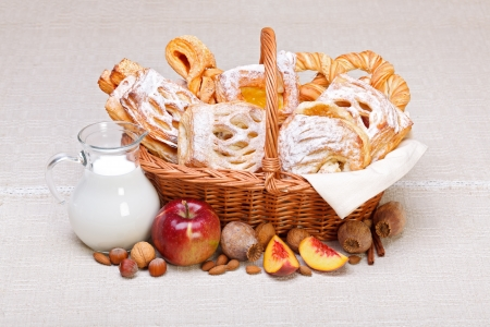 Lots of sweet cakes in basket, fruit and milk decoration around Stock Photo - 17688266