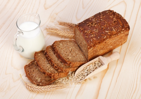 Brown sliced bread with seeds and jug of milk on wooden board Stock Photo - 17688246