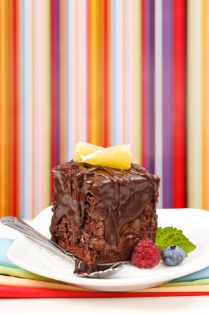 Cake with a chocolate gloss garnished with berries in front of colorful striped background - copy space above Stock Photo - 17688243