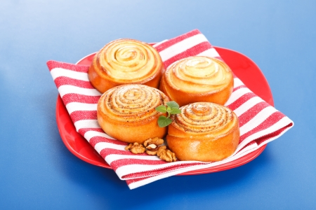 Four cinnamon rolls on red plate, blue background Stock Photo - 17688263