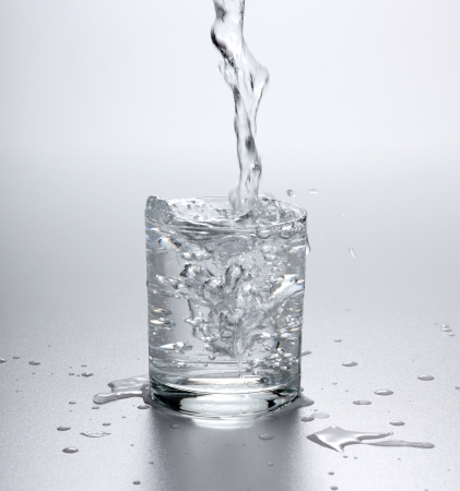 Water flowing into full glass, splashes around Stock Photo - 17688172