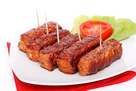 albondigas: Comida tradicional rumano - Rollos de carne con volantes - mititei, mici - servido con ensalada y tomate