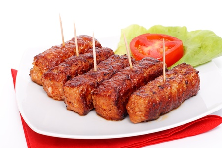 Traditional romanian food - frilled meat rolls - mititei, mici - served with salad and tomato Foto de archivo