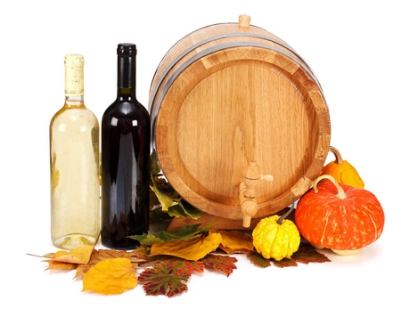Composition of wooden barrel, glass bottles, autumn leaves and several decorative pumpkins on white background Stock Photo - 17688184