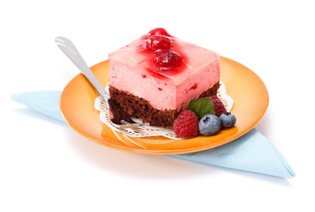 Raspberry yoghurt cake and jelly garnished with berries on small yellow plate Stock Photo - 17688131