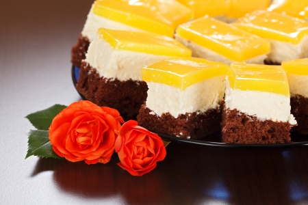 Closeup view of three-layered yoghurt cakes with red roses on brown background Stock Photo - 19111941