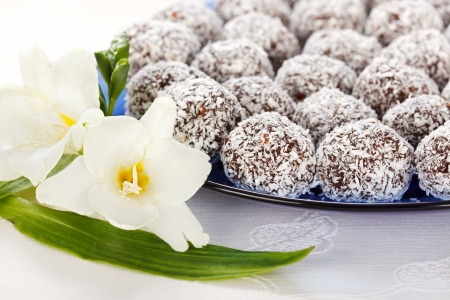 Closeup view of several snowball cake rolled in shredded coconut on blue plate with white flower Stock Photo - 19112015