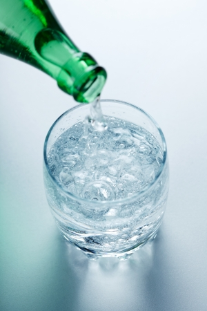 Top view of mineral water being poured into glass from green bottle